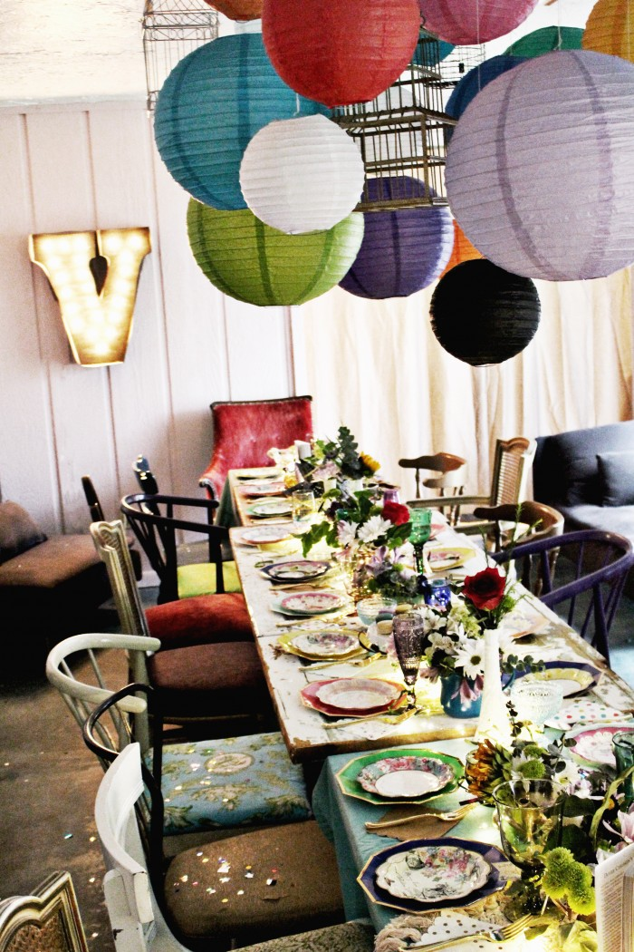 paper lanterns and birdcages above a mixed vintage table setting