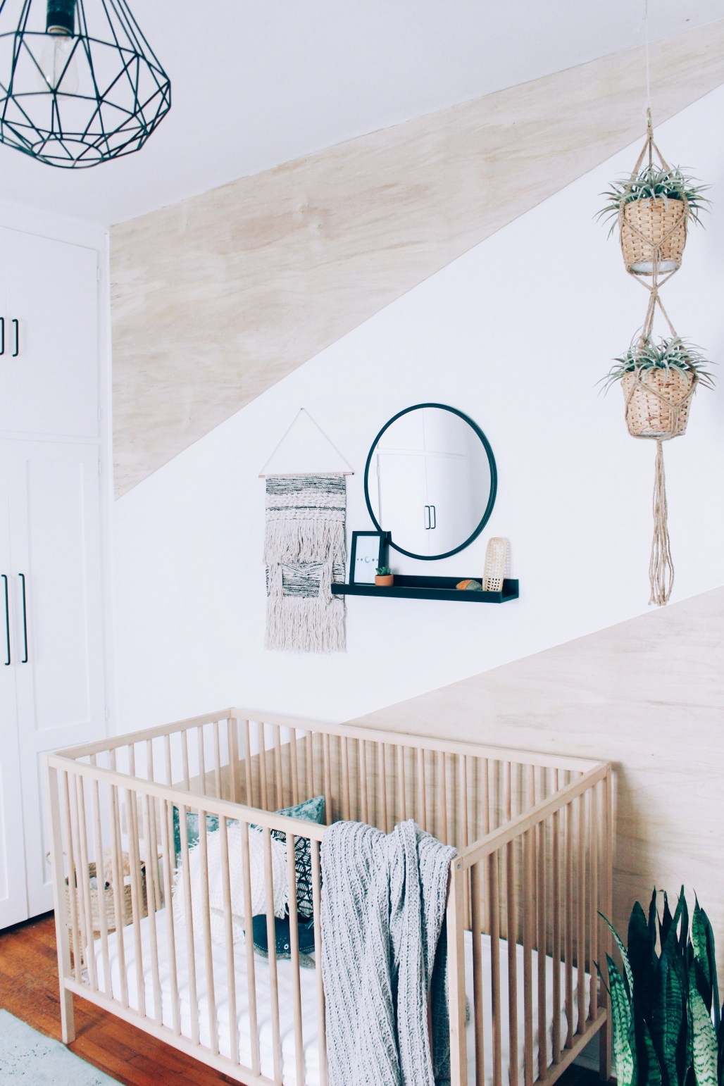Boy's nursery with plywood geometric wall DIY and lots of greenery and plants