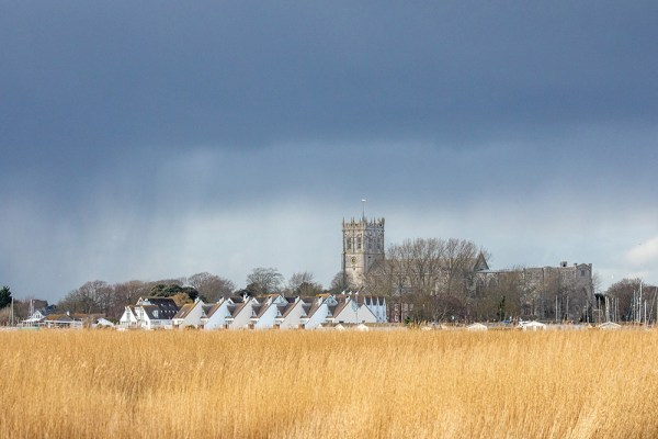 Christchurch Priory from Stanpit Marshes under rain clouds