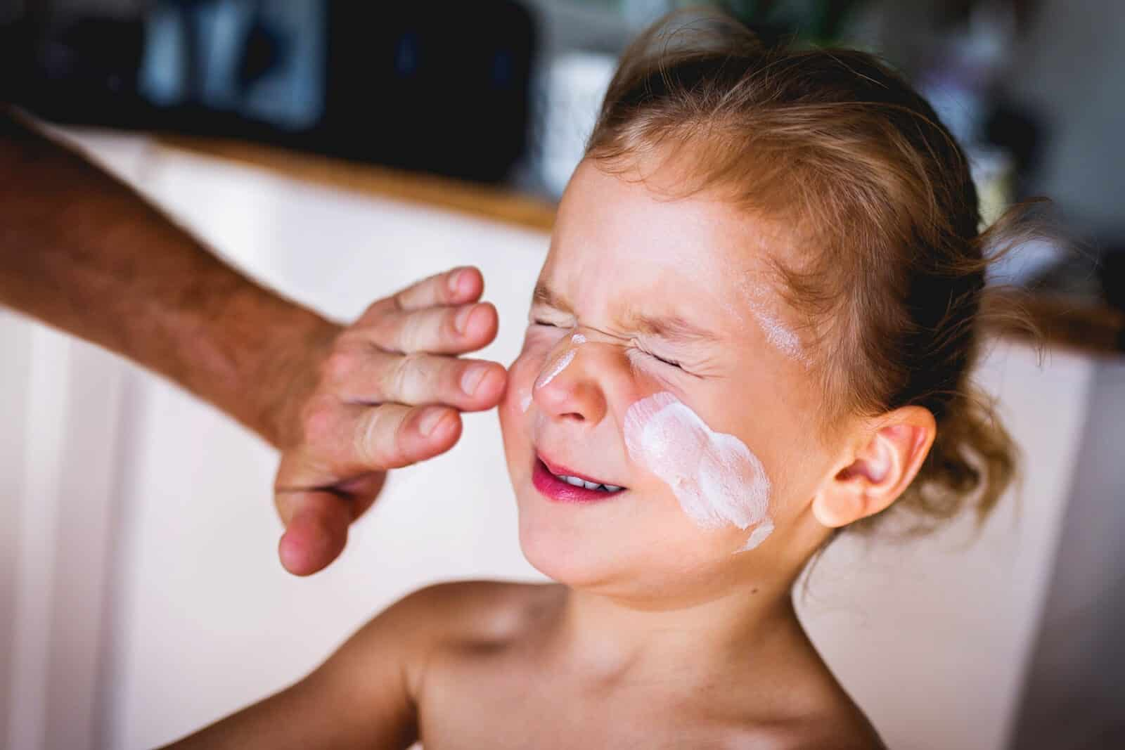 applying sunscreen on boys face