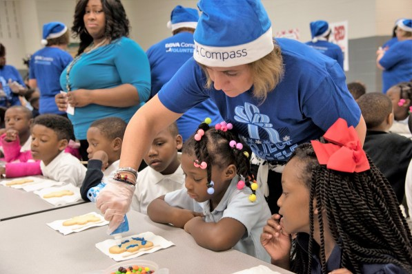 BBVA Compass employees donned their blue apparel to give the South Hampton kids a lesson about saving in the midst of fun activities such as decorating and eating cookies. (Brittany Faush / Alabama NewsCenter)