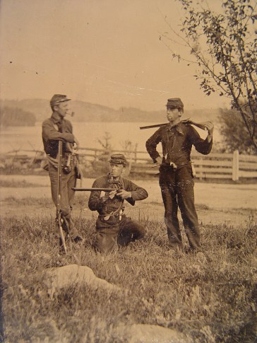 Three unidentified young soldiers in uniforms with shotguns, musket and pipes in a field with a fence in the background, 1861 – 1865. (Liljenquist Family Collection of Civil War Photographs, Library of Congress, Prints and Photographs Division)