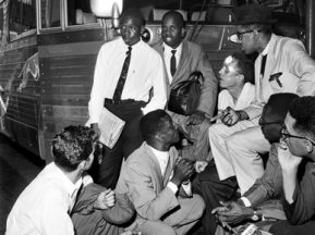 Fred Shuttlesworth, crouching center, and Freedom Riders discuss plans at the Birmingham Greyhound Terminal after drivers refused them service. Freedom Riders are, clockwise from left: Ed Blankenheim (kneeling), Charles Person, Theodore Gaffney, James Peck, the Rev. Benjamin Cox, Moses Newson and Simeon Booker. (From Encyclopedia of Alabama, courtesy of The Birmingham News)