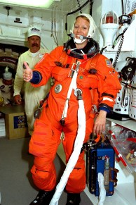 """The crew of STS-90 participates in Terminal Countdown Demonstration Test (TCDT) activities at KSC's Launch Pad 39B. The TCDT is held at KSC prior to each space shuttle flight to provide crews with the opportunity to participate in simulated countdown activities. Here, Mission Specialist Kathryn """"Kay"""" Hire gives a """"thumbs up"""" to the mission after being suited up in her orange launch and re-entry suit. (NASA)"""