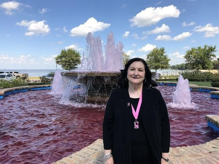 Feltus takes a break at the fountain at Pier Park in Fairhope, whose waters are dyed pink in honor of Breast Cancer Awareness Month. (Donna Cope/Alabama NewsCenter)