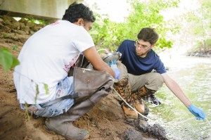 Graduate students Parnab Das, left, and Aaron Blackwell, graduate students in Dr. Mark Elliott's lab, collect water from Big Prairie Creek outside Newbern for an earlier project. (University of Alabama)