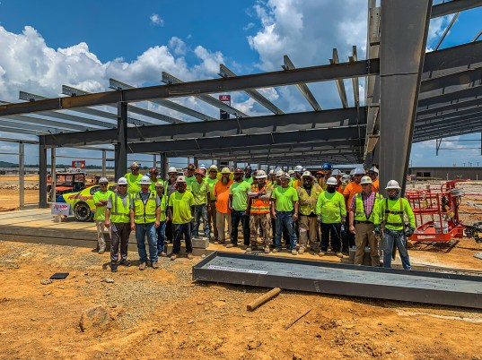 Construction crews pose for a picture in front of the steel frame of the Open Air Club at Talladega Superspeedway. (Dennis Washington / Alabama NewsCenter)