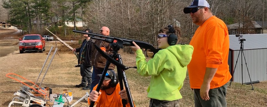 Drake Arden is helped by volunteers as he learns how to shoot a shotgun. (Dennis Washington / Alabama NewsCenter)