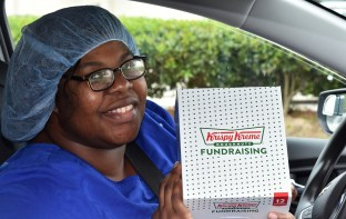 Brittney Payne, sterile tech at UAB Highlands, holds a complimentary box of Krispy Kreme doughnuts. The company is offering free doughnuts to all front-line workers each Monday during the COVID-19 pandemic. (Solomon Crenshaw Jr./Alabama NewsCenter)