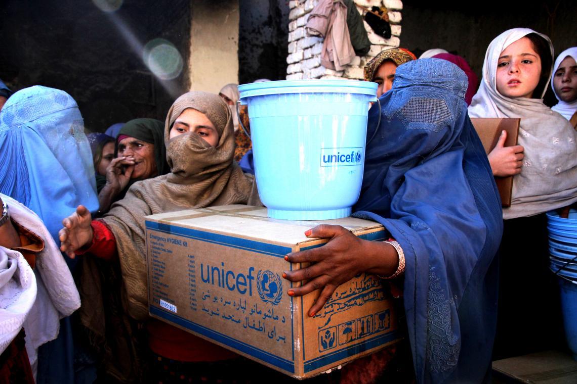 Flickor bär förnödenheter från UNICEF