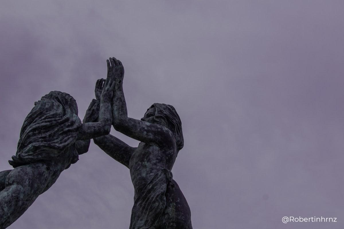 Escultura en Playa del Carmen de un hombre y mujer levantando las manos.