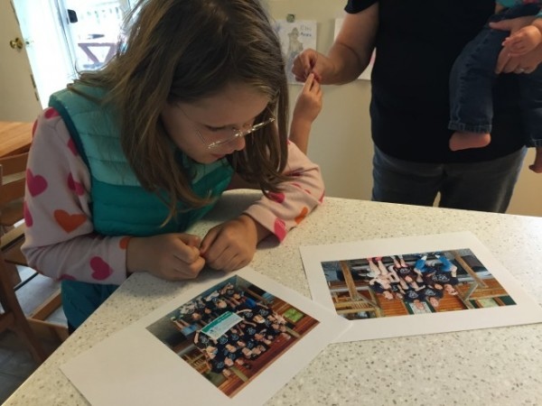 Elena Lohrey, 12, looks at pictures from an FASD Family Camp her family attended in Arizona earlier this summer. (Photo by Lisa Phu/KTOO)