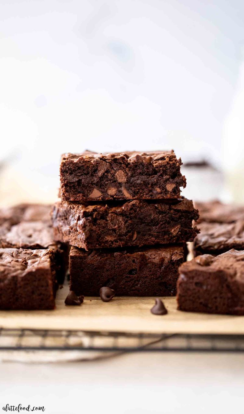 stack of chocolate fudge brownies with cocoa powder and chocolate chips on brown parchment paper