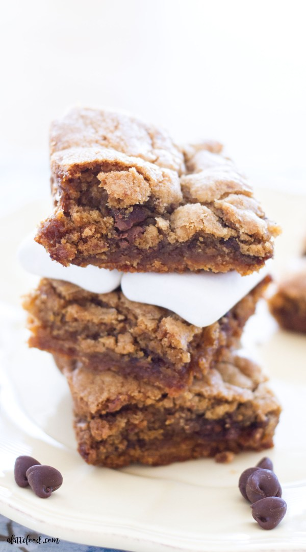 These S'more Chocolate Chip Cookie Bars are rich, gooey, and full of the classic campfire s'more taste! This easy S'more Chocolate Chip Cookie Bar recipe is part chocolate chip cookie and part s'more, making this such a fun summer dessert!