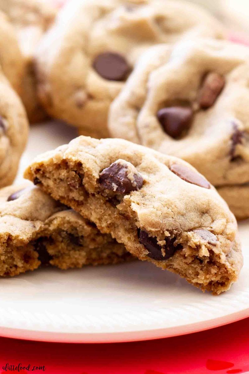 a dark chocolate chip toffee cookie broken in half to see the soft gooey inside