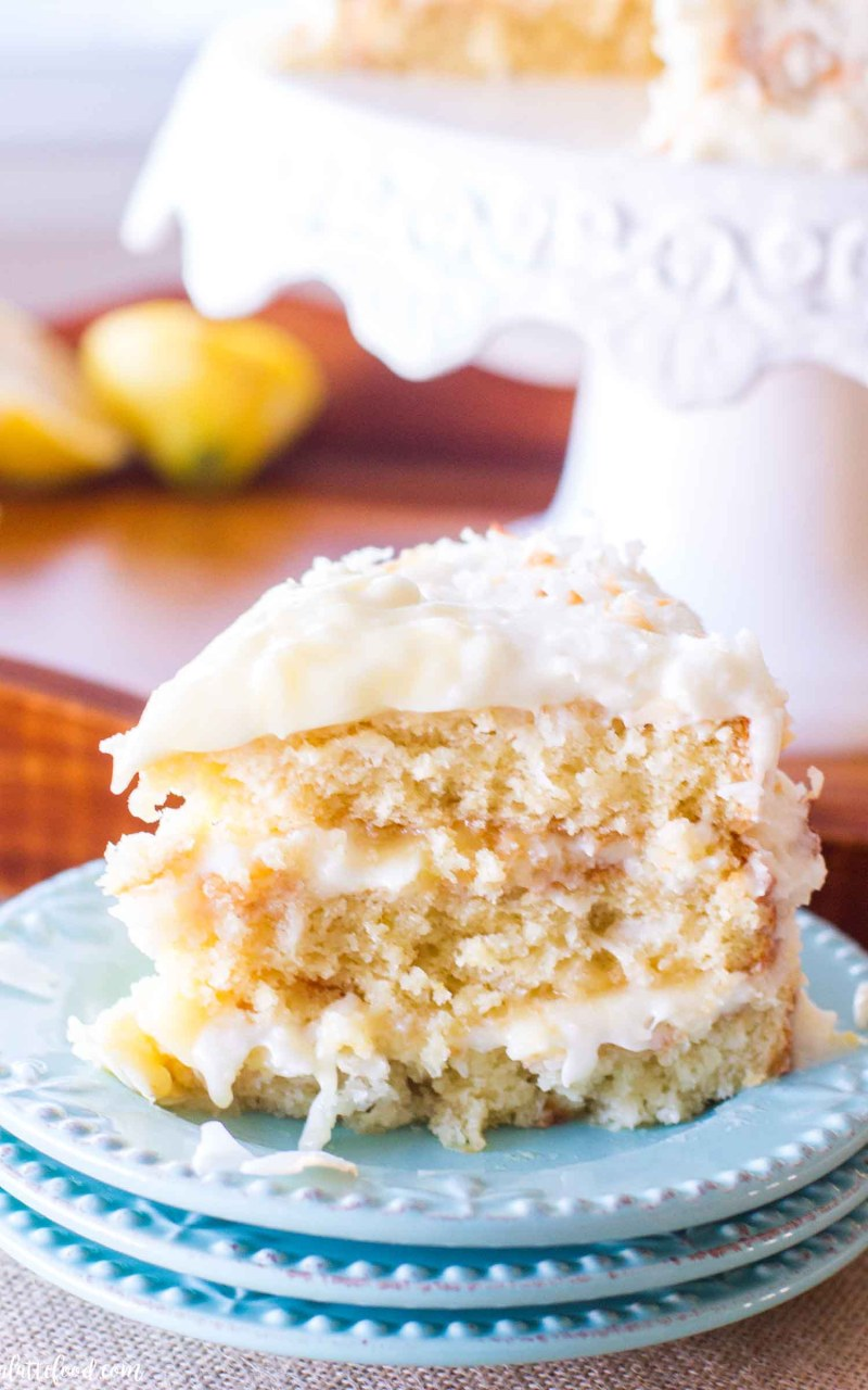 coconut lemon cake with frosting on stack of plates