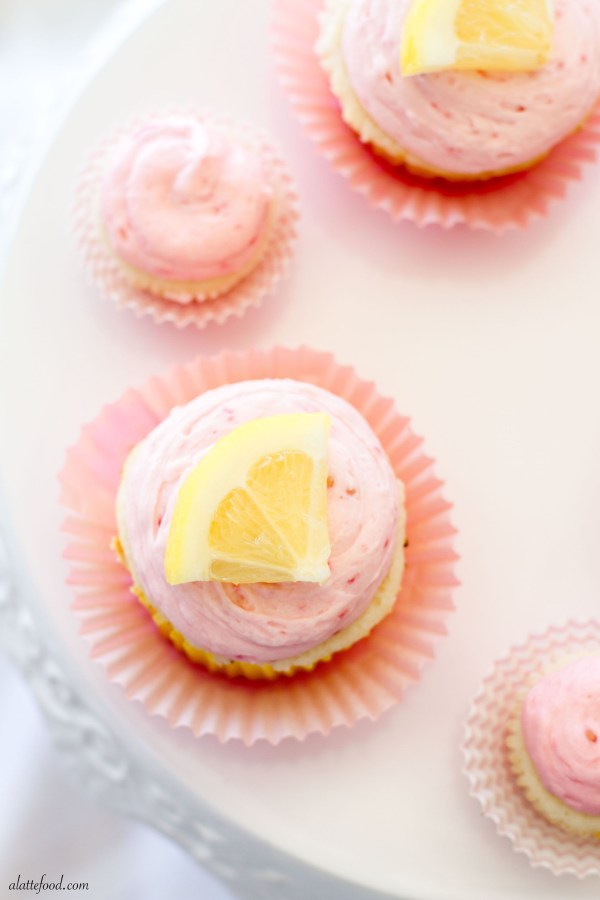 These fluffy lemon cupcakes are filled with tangy lemon curd and and topped with rich raspberry buttercream!| www.alattefood.com