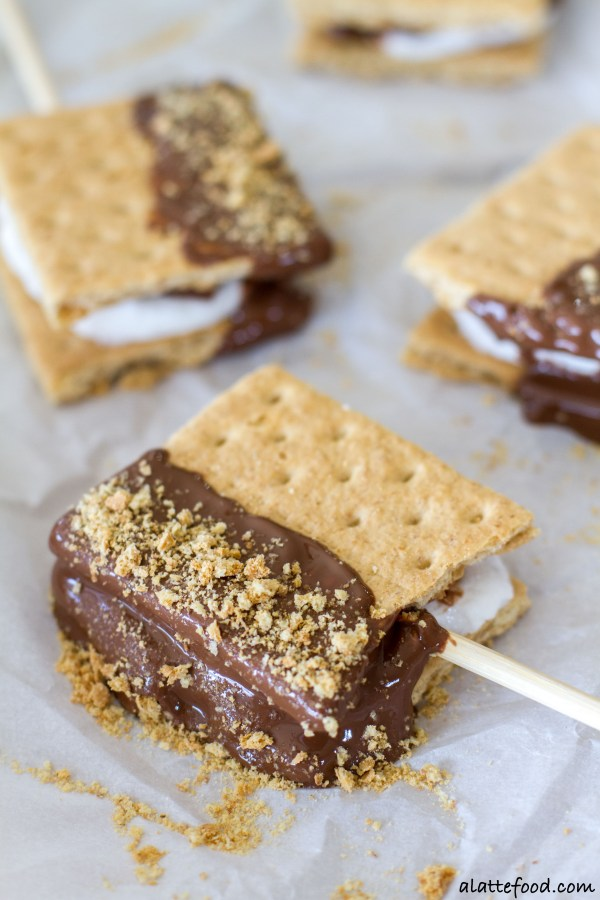 These fun, tasty s'mores pops have all the campfire taste without the campfire! Made indoors, you can have these s'mores any day of the week! Plus, each mallow is stuffed with a Hershey's Rolo!| www.alattefood.com