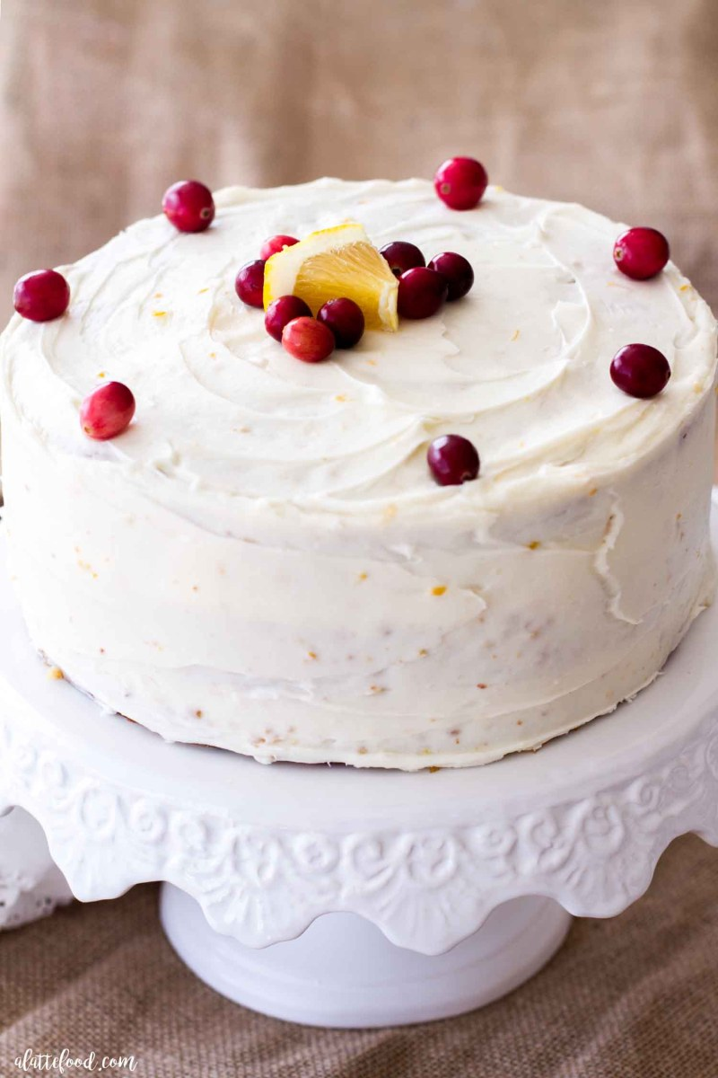 orange cream cheese frosted cranberry cake with fresh oranges and cranberries