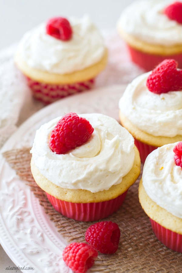 These sweet orange cupcakes are filled with a homemade raspberry cream and topped with an orange buttercream frosting! The flavors of spring in one simple homemade raspberry orange cupcake recipe. | www.alattefood.com