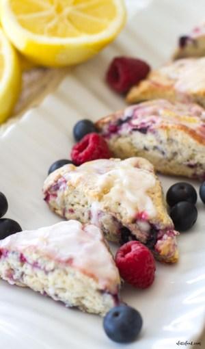mini mixed berry scones with lemon glaze on white serving platter