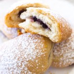 These baked beignets can be whipped up in a matter of minutes and are filled with a sweet blueberry orange jam! Rolled in cinnamon sugar and topped with powdered sugar and orange zest, this easy beignet recipe is sure to be a hit at your next breakfast or brunch!