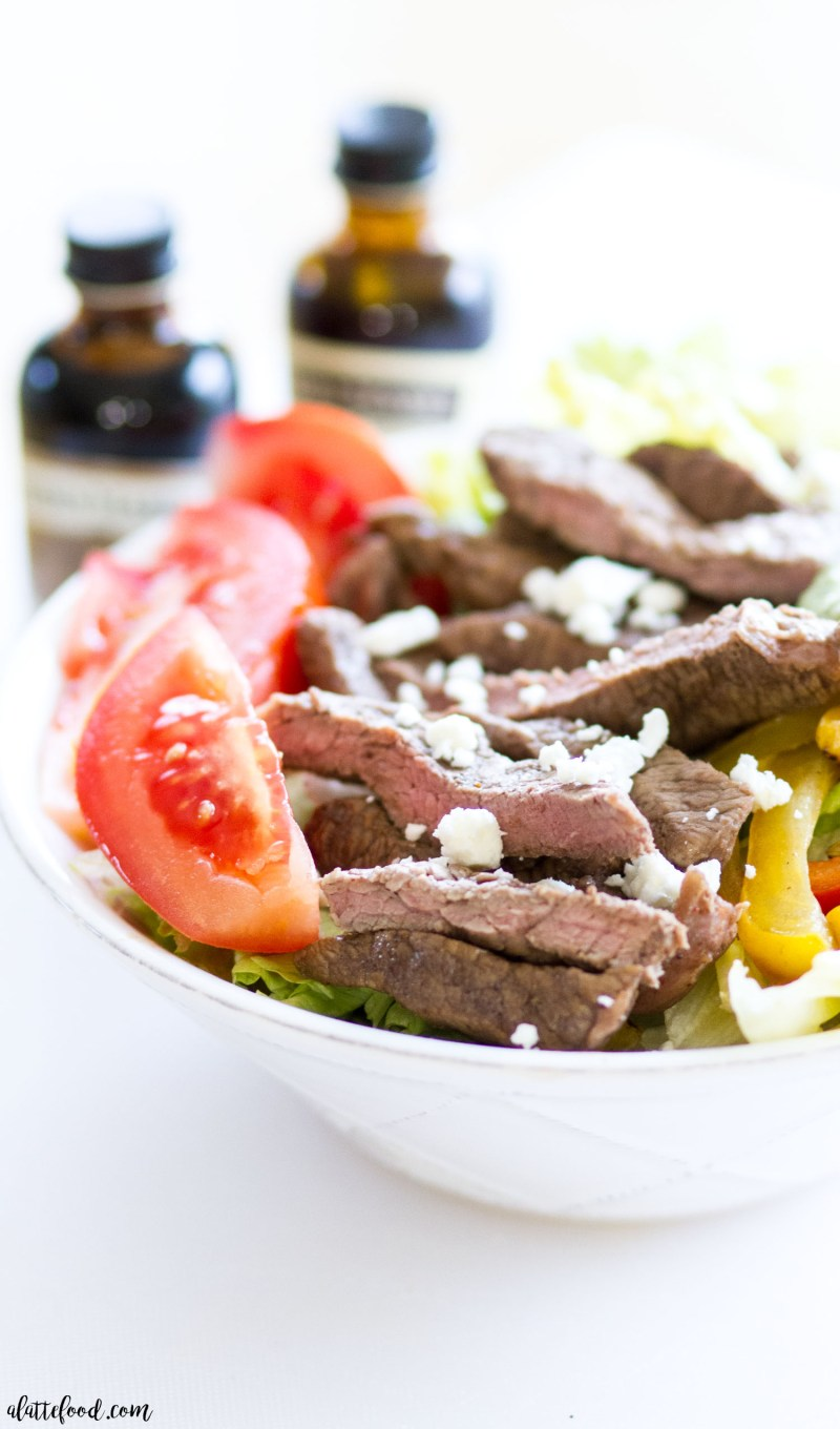 This Fajita Steak Salad with Cilantro Avocado Dressing is made with flank steak, a coffee marinade, and grilled peppers and corn! Topped with a homemade cilantro avocado dressing, cotija cheese, and tomatoes, this fajita steak salad is sure to be a weeknight dinner staple! Plus, a step-by-step video below!