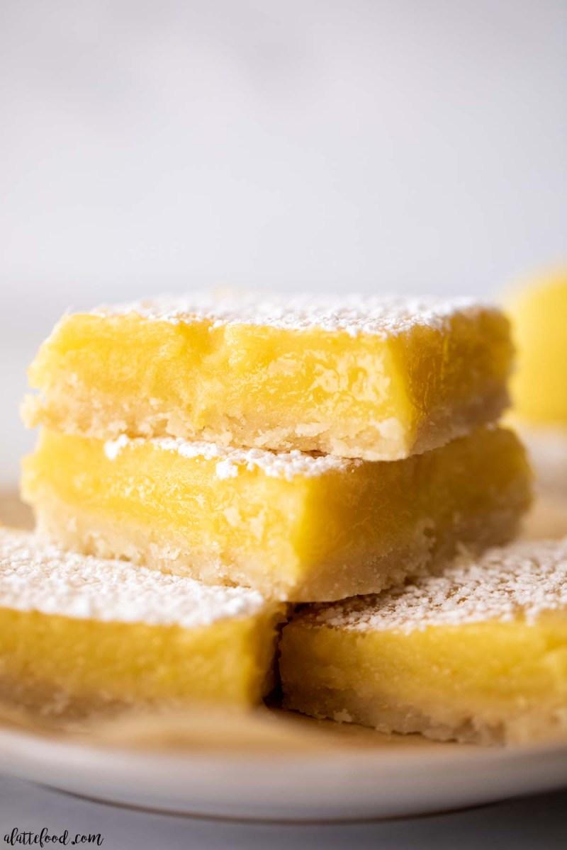 shortbread crusted lemon bars stacked on white plate