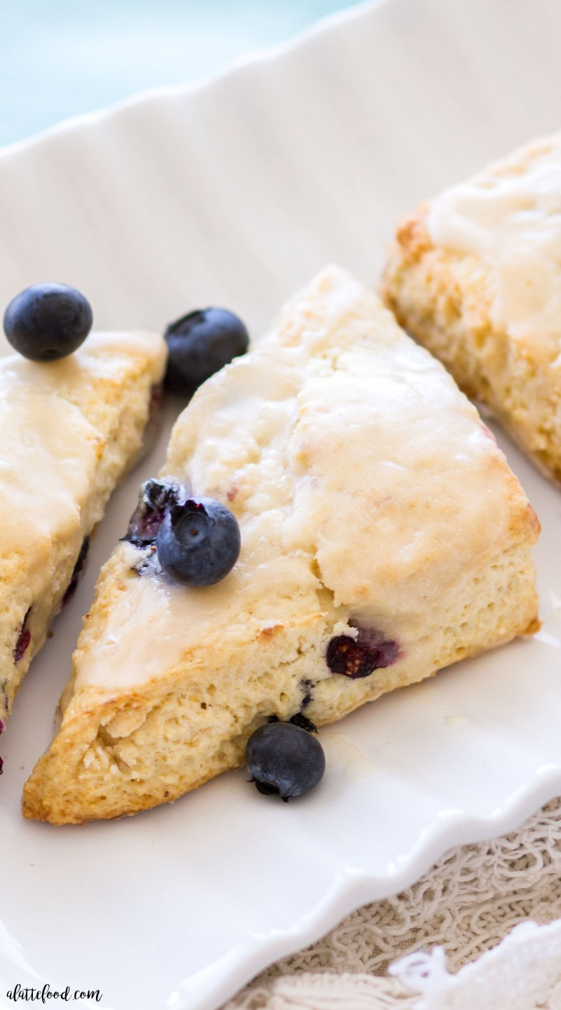 These homemade blueberry cream cheese scones are sweet, flaky, and topped with a vanilla glaze. Homemade blueberry scones are so simple to make, and are perfect for a quick and easy breakfast, snack, or dessert! homemade scones, blueberry scones, how to make scones