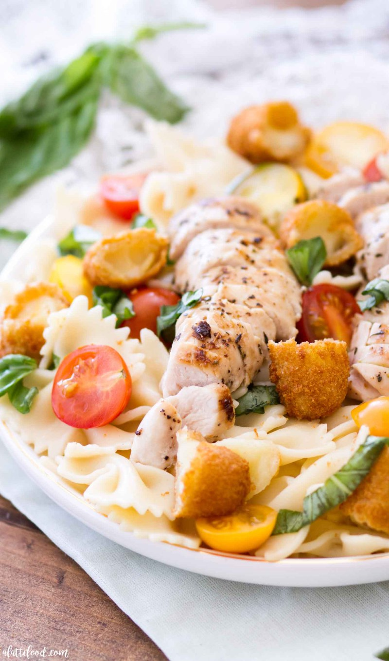This Chicken Caprese Pasta is filled with fresh basil, grilled chicken, tomatoes, and Mozzarella Sticks, kicking the classic caprese salad recipe up a notch. The texture and flavor of the Mozzarella Sticks pairs perfectly with the pasta and chicken, the fresh basil and tomatoes bring the whole dish together, making a simple dinner recipe that is full of flavor!