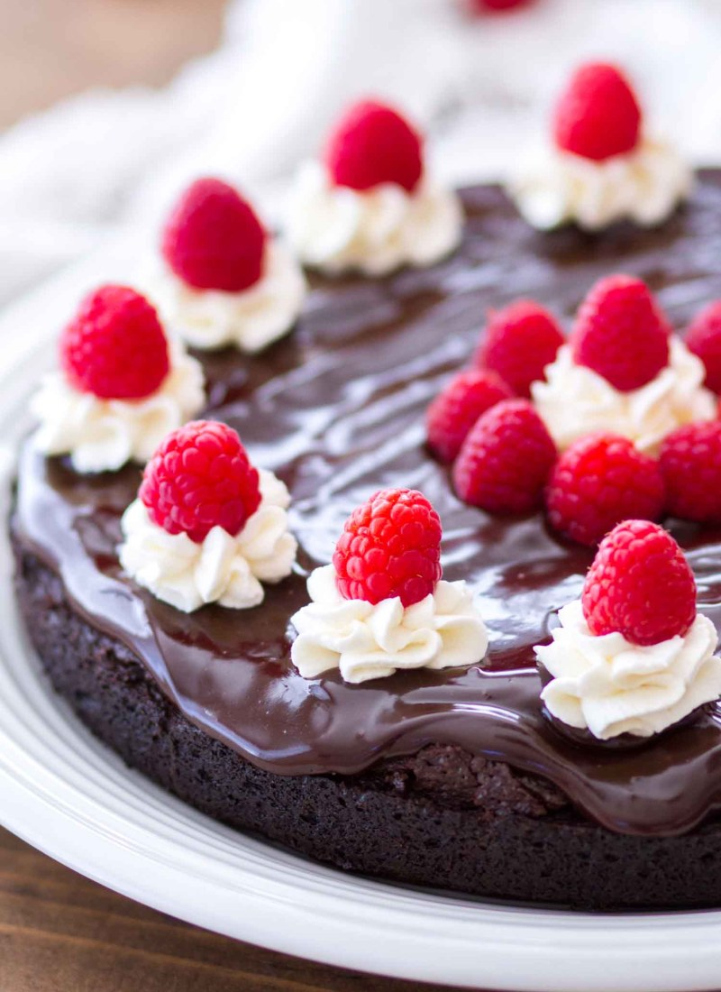This Mocha Flourless Chocolate Cake is topped with a chocolate ganache and a whipped cream frosting.This easy homemade chocolate cake is rich, fudgy, and full of intense chocolate flavor. This is a perfect Valentine's Day dessert, or the perfect chocolate dessert for any day of the week! Plus, it's a great gluten-free dessert too!