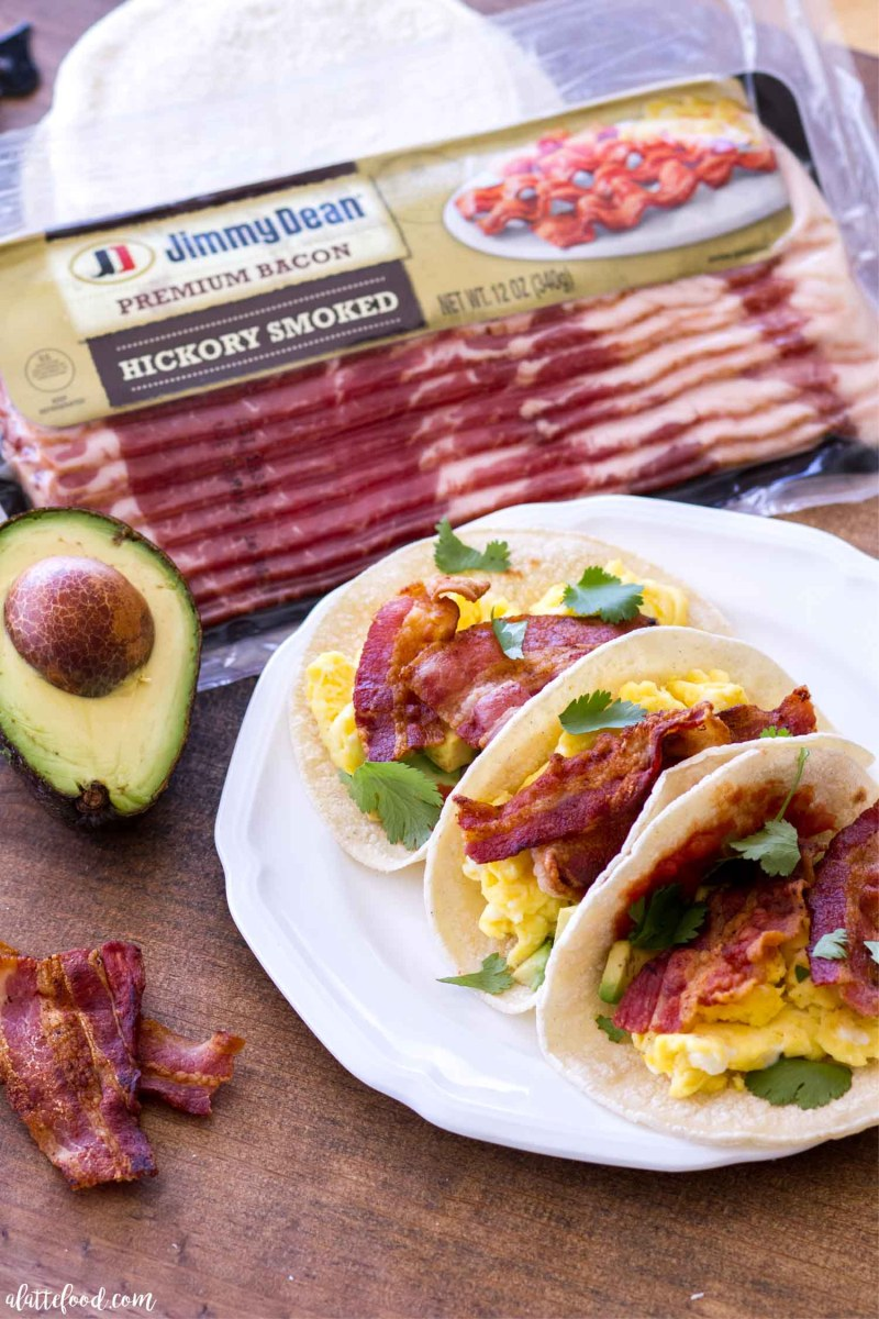 These Egg and Bacon Breakfast Tacos are full of hickory smoked bacon (Jimmy Dean® Bacon), fluffy scrambled eggs, salsa, cilantro, and avocado. Served on corn tortillas or flour tortillas, this breakfast taco recipe is sure to be an easy breakfast staple. This hearty breakfast recipe is perfect for Father's Day, but easy enough to whip up any day of the week! easy egg tacos, how to make scrambled eggs, the best scrambled eggs