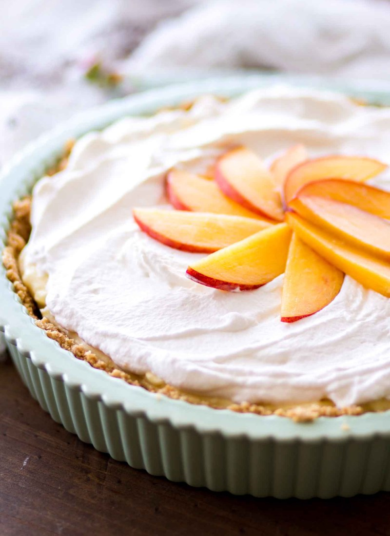 peach cream pie in green dish with whipped cream and fresh peach slices
