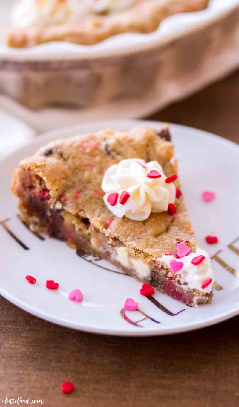 This slice of Chocolate Chip Funfetti Cookie Cake is topped with a vanilla frosting.