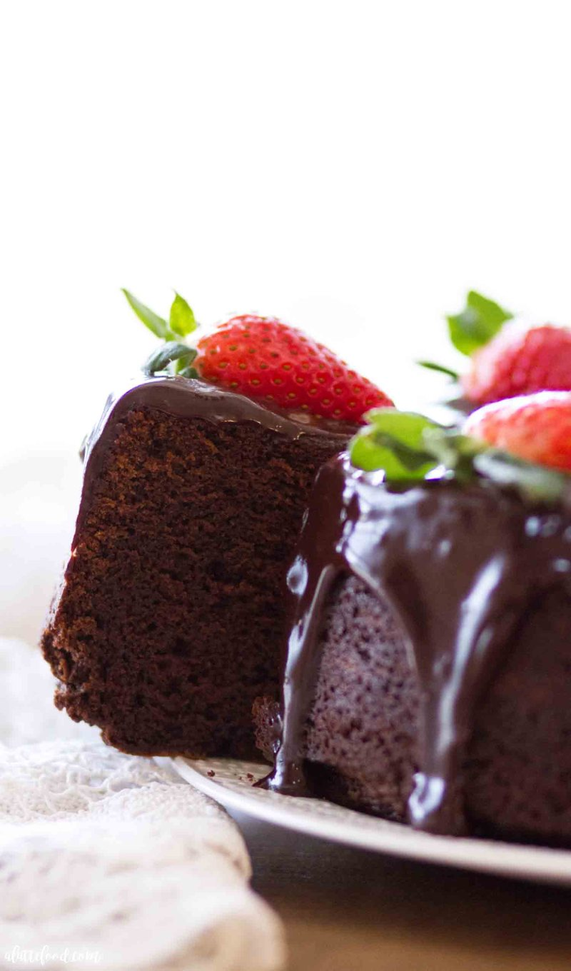 chocolate pound cake with ganache sliced and served with strawberries