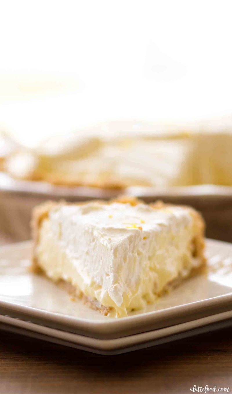 No Bake Lemon Cream Pie slice topped with lemon whipped cream and a golden oreo crust