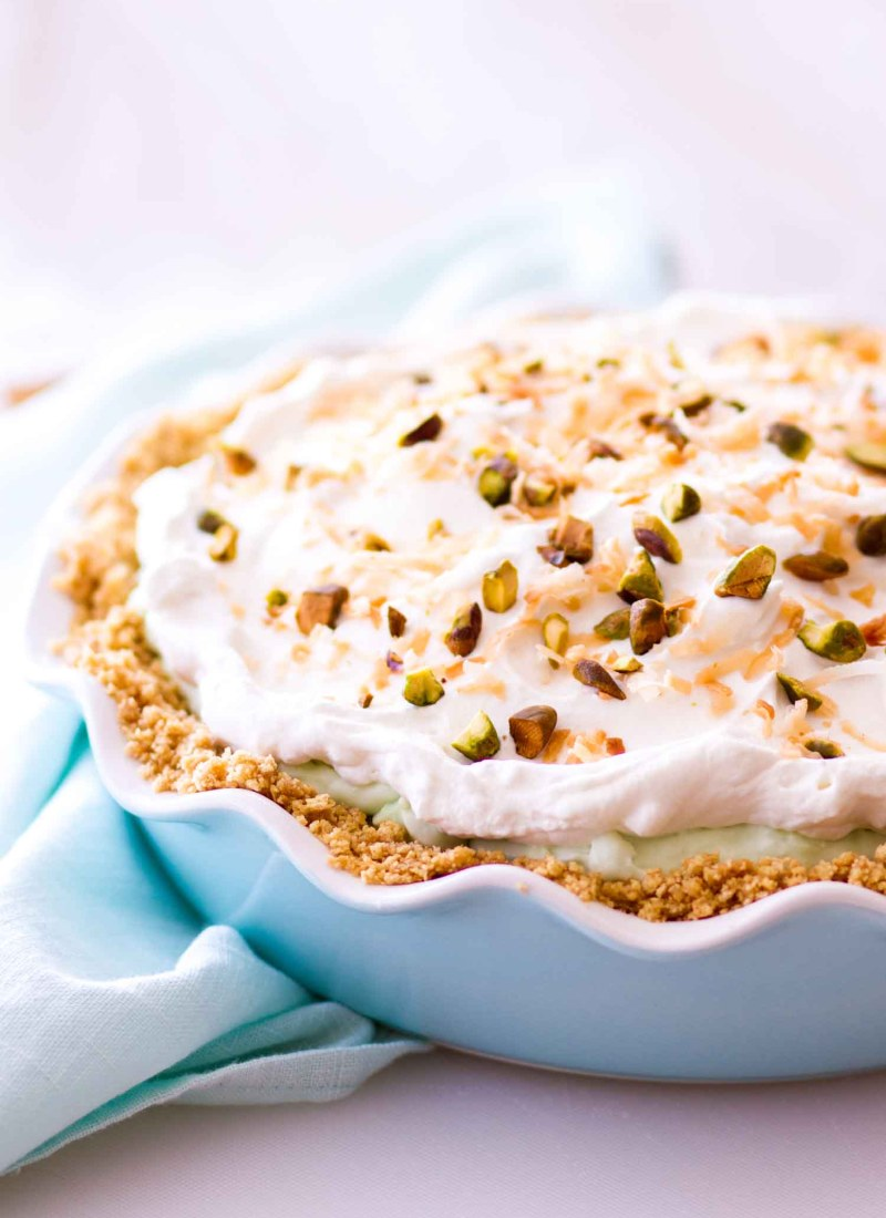 pistachio pudding cream pie in a graham cracker crust inside a blue pie plate