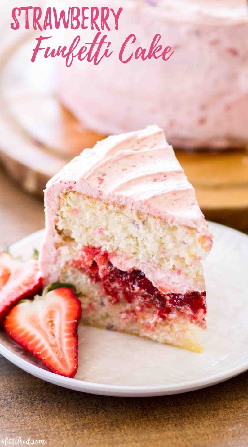 Slice of strawberry funfetti cake filled with fresh strawberry cake filling and strawberry frosting