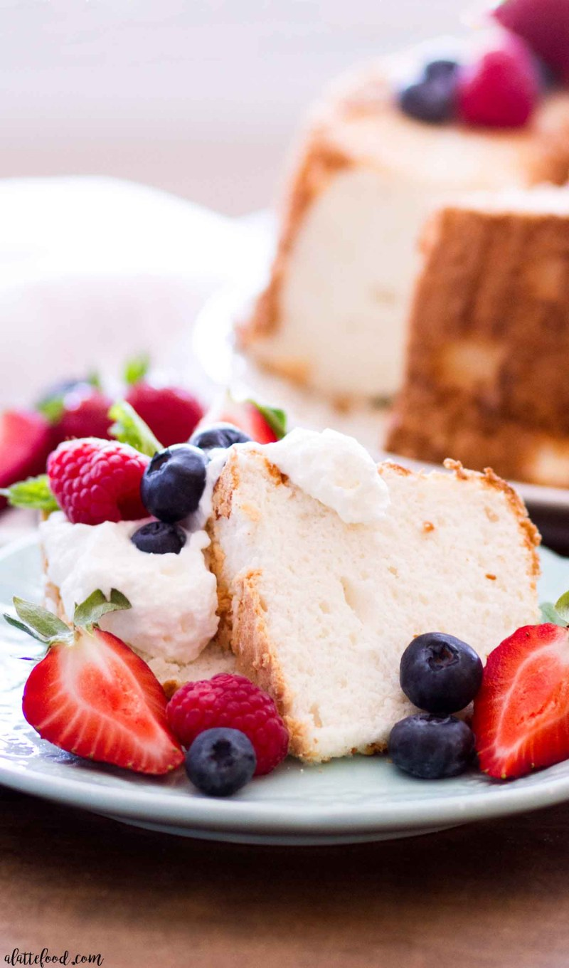 angel food cake slice on a blue plate with strawberries and blueberries