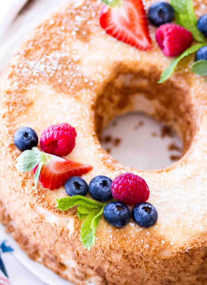 This easy homemade angel food cake recipe is topped with fresh berries and powdered sugar