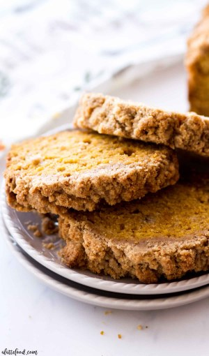 Three slices of pumpkin bread with streusel on a gray plate