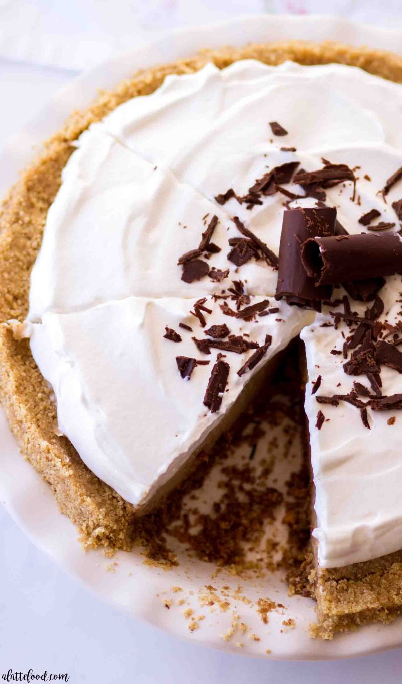 Peanut butter custard pie with whipped cream in a white pie plate