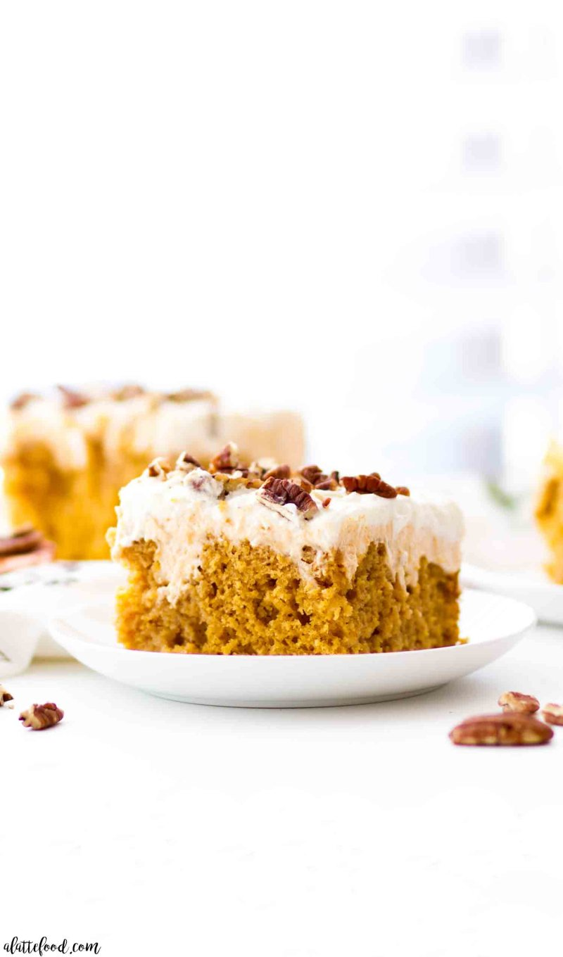 Pumpkin  Poke Cake with cream cheese frosting on white plate