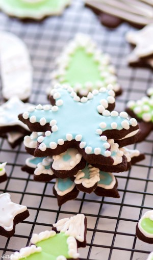 snowflake cookies decorated with royal icing stacked on top of each other