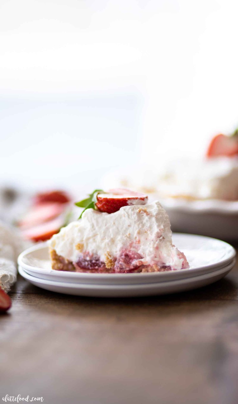 Slice of marshmallow strawberry pie on stacked white plates