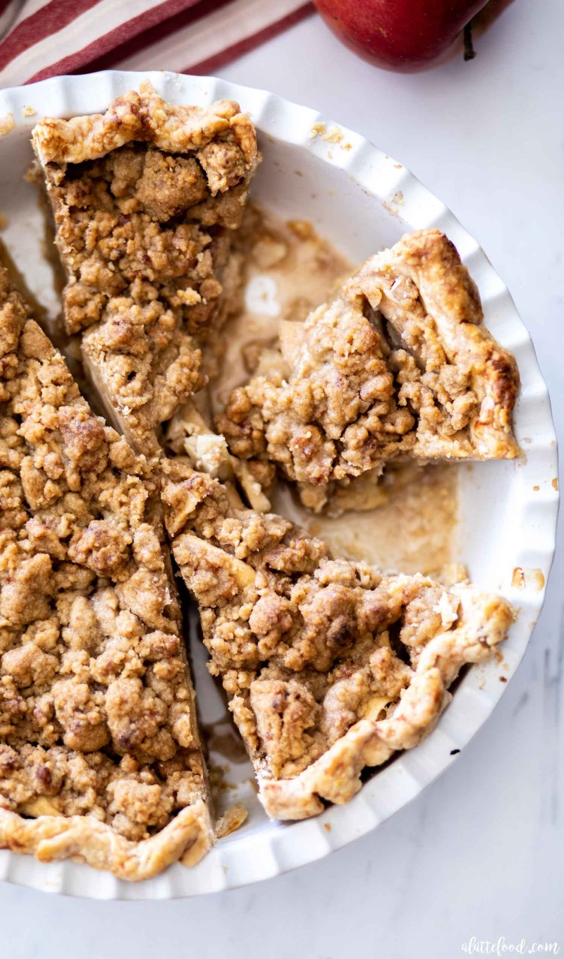 cut apple crumb pie in a white pie dish