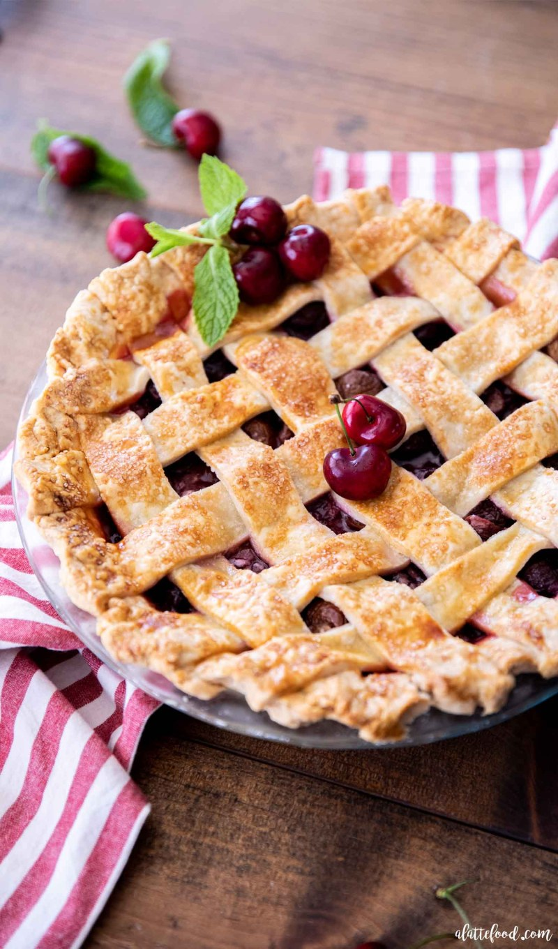 whole cherry pie with lattice crust on wood counter