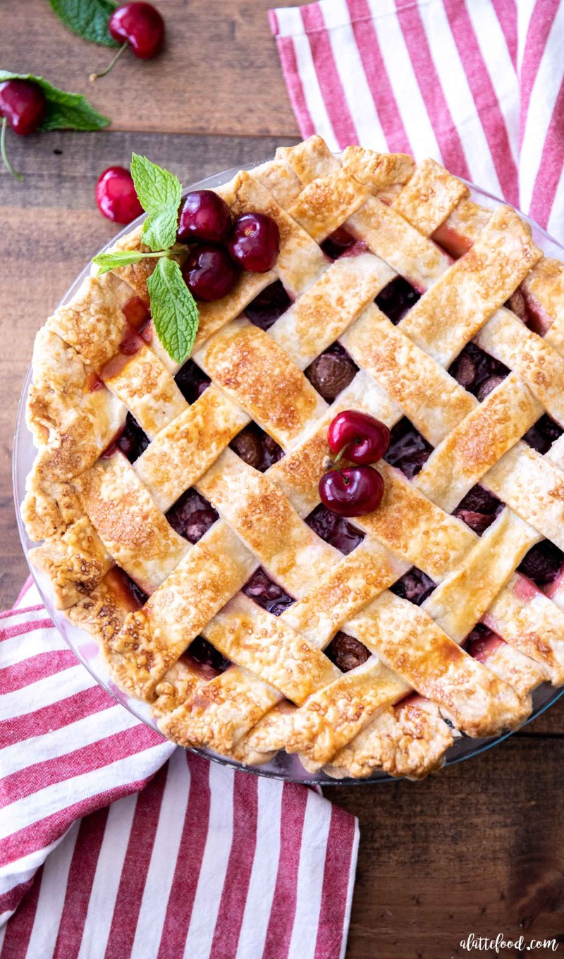 baked sweet cherry pie on red striped towel
