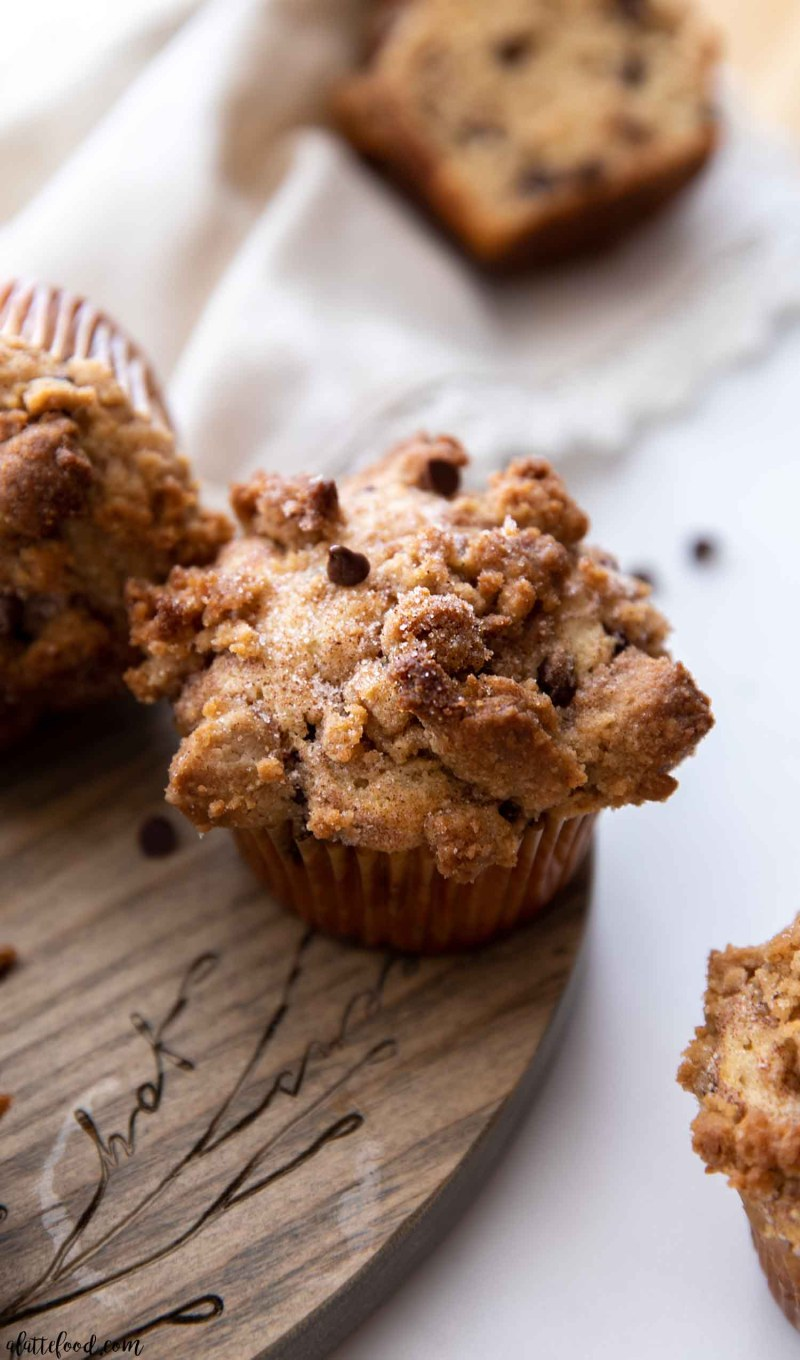 chocolate chip muffin with crumb topping on wooden cutting board