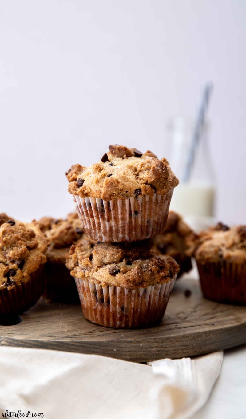 baked chocolate chip muffins stacked on wooden cutting board